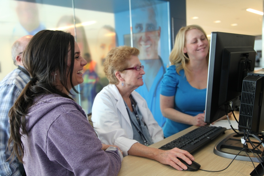 Jessica Sauls (far right), of Information Systems, with respiratory therapists Gabriella Andrade (at left) and Jane Bartholomew in the eCare information center
