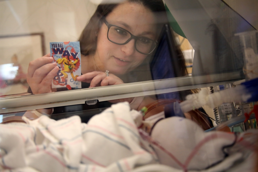 Rachel Ovaginian shows her son, Cameron, a valentine made for them by a donor from the Kraft Family Blood Donor Center.